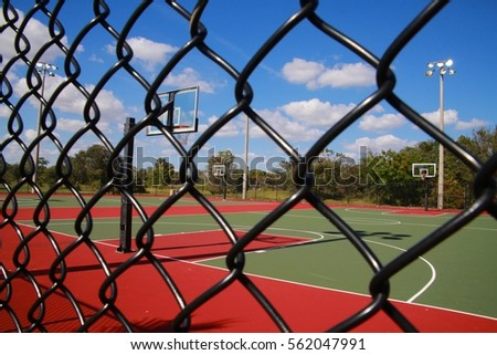 Empty Basketball Court with Hoops Seen Through Chain-Link Fence, Quiet Waters Park, Deerfield Beach, FL, Afternoon in January #562047991