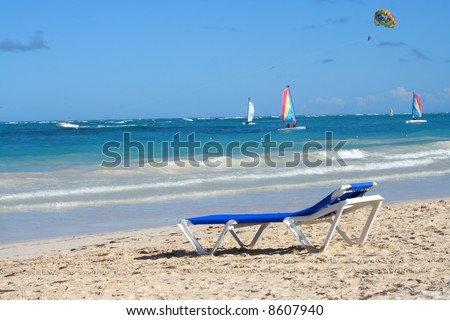 empty beach chair overlooking the ocean with boats on the Caribbean shore of Bavaro beach, Punta Cana in the Dominican Republic