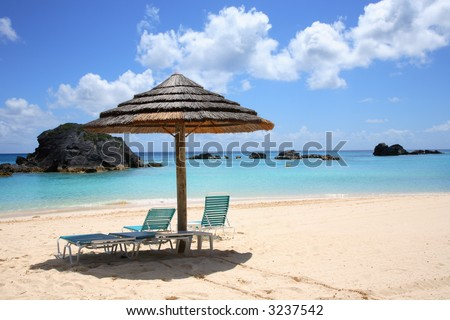 empty beach chairs look out over the crystal blue/green waters of Bermuda in the Carribbean
