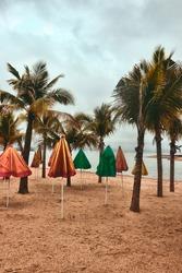 Empty beach, misty rain sky, palm trees, bungalows. A seaside resort in winter fog. South China sea, Vietnam winter recreation. Halong Bay on background