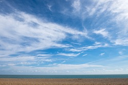 Empty beach with a blue sky and wispy cloudscape. Aldeburgh Beach, Aldeburgh, Suffolk UK.