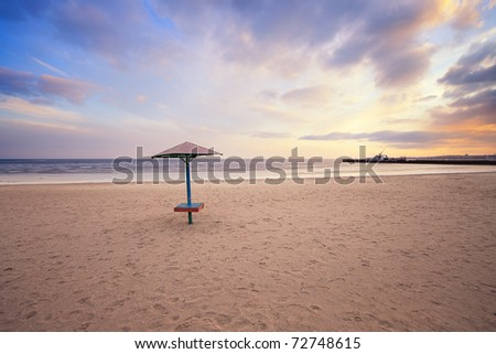 empty beach with lonely umbrella at sunset