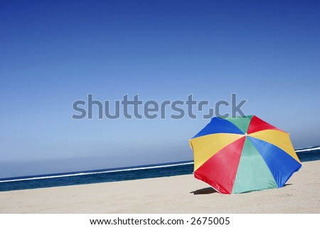 Empty beach with single rainbow colored parasol