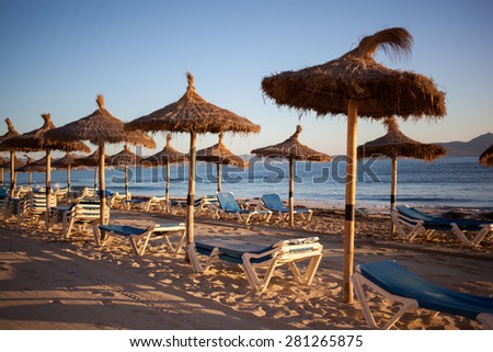 Empty beach with straw umbrellas on sunrise in Spain, Mallorca