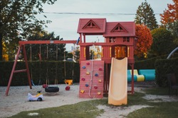 Empty beautiful modern playground with swings and a slide in the park Children outdoor activities concept.