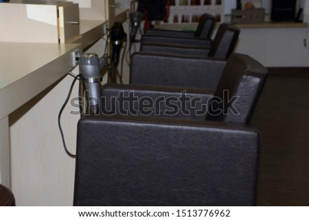 empty beauty salon with armchairs and hairdryer, interior of a modern hairdressing salon with armchairs in a row