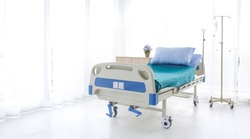 Empty bed in a hospital room.blue and white hospital bed on white background. Patient room and insurance concept.
