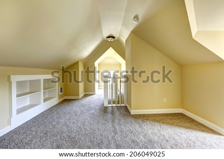 Empty bedroom in soft ivory with soft brown carpet floor and vaulted ceiling