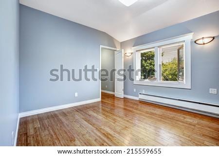 Empty bedroom with light blue walls and new hardwood floor