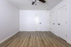 Empty bedroom with open doors leading to the livingroom, bathroom and a closet