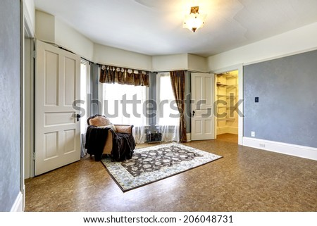 Empty bedroom with walk-in closet. Decorated with single antique armchair