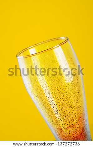 Empty beer glass with water drops on yellow background