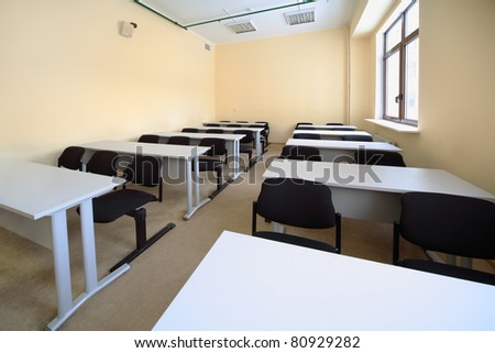 Empty beige classroom with wooden school desks and simple black chairs