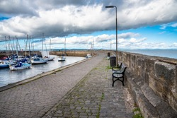 Empty Bench along a Cobblestone Path on a Quay. Some Sailing Boats in Harbour are Visible on the Left Side of the Photo.