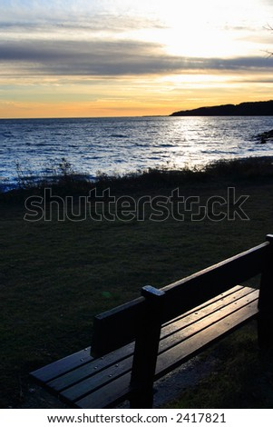 Empty bench by the lake in the light of dawn