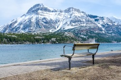 Empty bench on the waterfront with an amazing view of a lake & snow covered mountains in Waterton Lakes National Park, Alberta, Canada