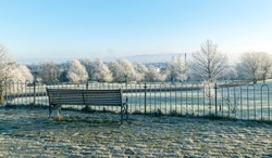 Empty bench overlooking Queen's Park, Glasgow, Scotland on a frosty and misty winter morning.
