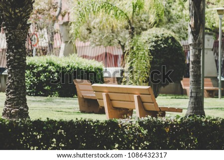 Empty benches inside a beautiful park #1086432317