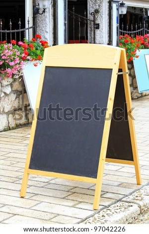 Empty black A board in front of restaurant