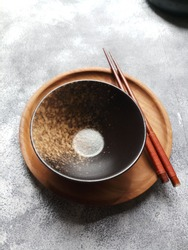 Empty black and grainy bowl on wooden plate with chopsticks. Grainy textured background