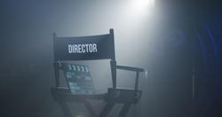 Empty black chair with sign Director and clapperboard in spotlight on filming set