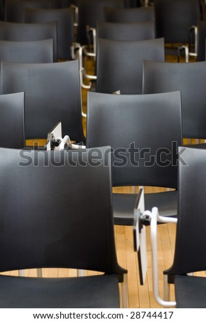 Empty black chairs in conference room. Shallow depth of field.
