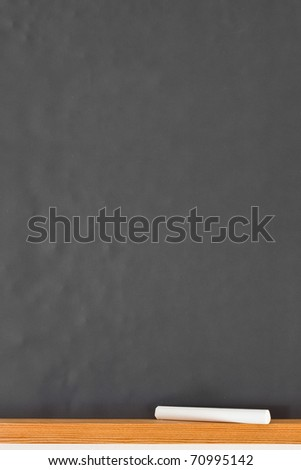 Empty black chalkboard with piece of chalk - stock photo