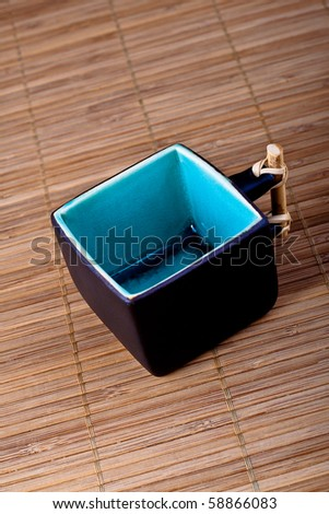 empty black handmade Asian teacup on bamboo mat