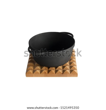empty black iron cast cauldron, cast iron black pot, kettle cookware on a cutting board, isolated on perfect white background, stock photography