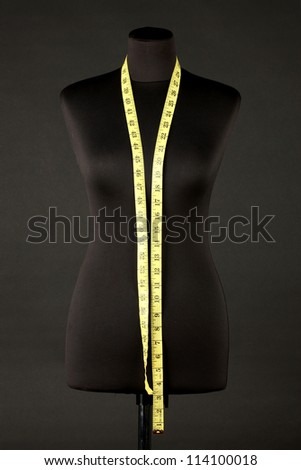 empty black mannequin with measuring tape isolated on black