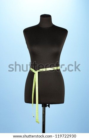 empty black mannequin with measuring tape  on blue background