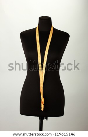empty black mannequin with measuring tape  on grey background