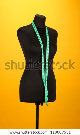 empty black mannequin with measuring tape  on orange background