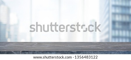 Empty black marble stone table top and blur glass window wall building banner mock up background - can used for display or montage your products. #1356483122