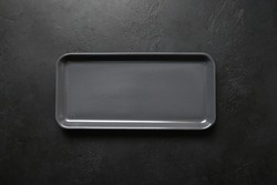 Empty black modern rectangular plate on black background. View from above. Copy space. Kitchen stuff, flat lay for cooking as background.