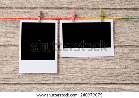 empty black photo frames hanging with clothespins on wooden background