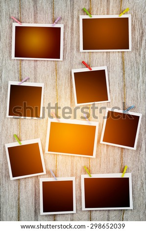 empty black photo frames hanging with clothespins on wooden background in vintage tone