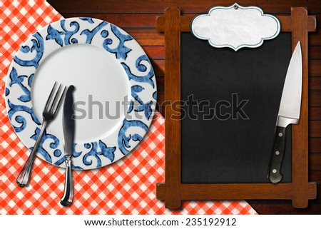 Empty Blackboard Plate and Cutlery / Empty plate with silver cutlery and kitchen knife, empty blackboard for recipes or menu with label on wooden table with red and white checkered tablecloth