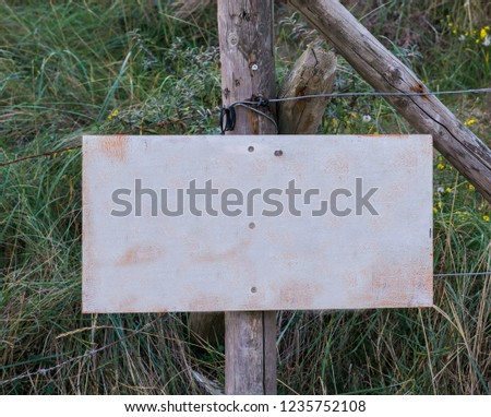 empty blank signboard plate on a pole to put whatever you want in a nature landscape with grass #1235752108