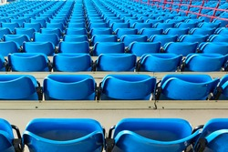 empty bleachers and chairs in blue indoor