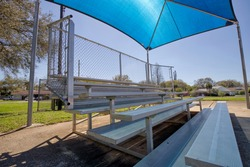Empty bleachers with a sunshade at a recreational ball field in Florida.
