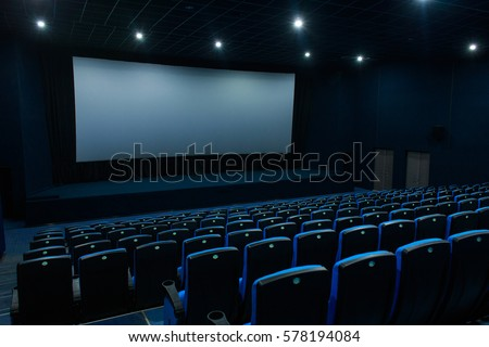 Empty blue cinema room with white screen and seats. Side view