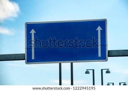 Empty blue road sign, white direction arrows. Blue sky #1222945195