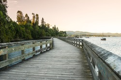 Empty boardwalk along the the shore of a bay at sunset. Some jetties with moored boats are visible in background.