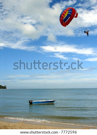Empty boat against parasailing & exotic cloudy blue sky