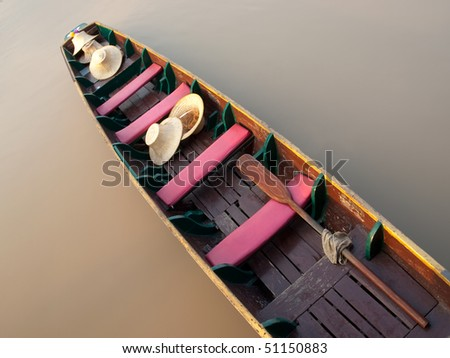 Empty boat floating on the calm river with only hats on it , closeup shot taken from above,SE Asia
