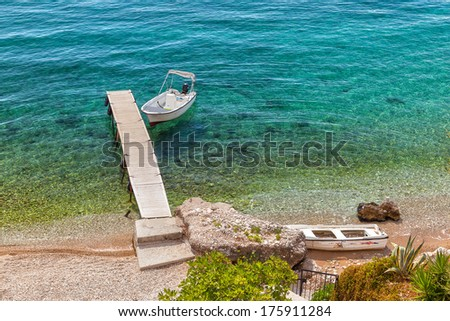 Empty boat standing at wooden pier under bright sunlight with shadow on pebbles at sea floor seen through transparent water, Corfu, Greece