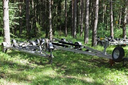 Empty boat trailers near trees on forest parking at Sunny summer day, watercrafts transportation