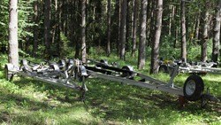 Empty boat trailers on forest parking at Sunny summer day, watercrafts transport storage