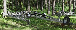 Empty boat trailers on forest parking at Sunny summer day, watercrafts transportation